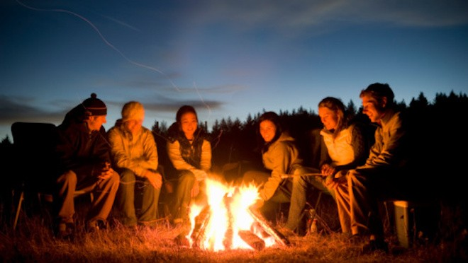 Six young people sitting around camp fire at dusk